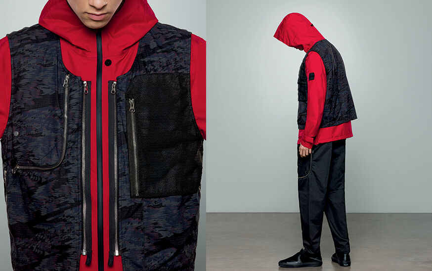 Two shots of the same model, showing the front close up and the back, wearing dark colored pants with zipper details, a bright red jacket with hood and a dark blue print vest with zipper details at chest.