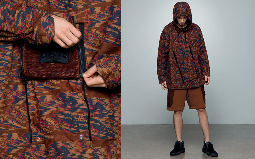 Two shots of the same model, one close up and one full body, showing a brown, blue and red print jacket with hood, chest diagonal zippers and brown cargo shorts with ribbed patch pockets.