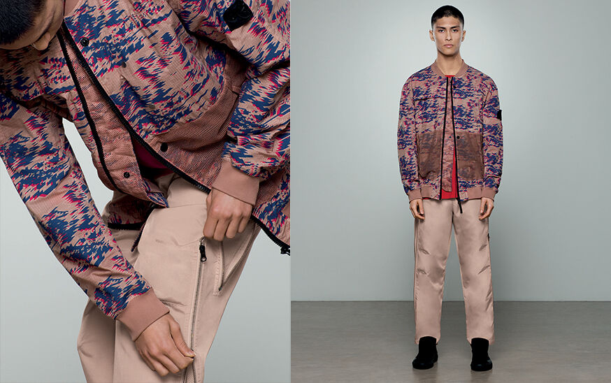 Two shots of the same model, one close up and one full body, wearing a khaki, blue and red print bomber jacket with black zipper fastening and beige pants with a two ways zipper on the left leg.