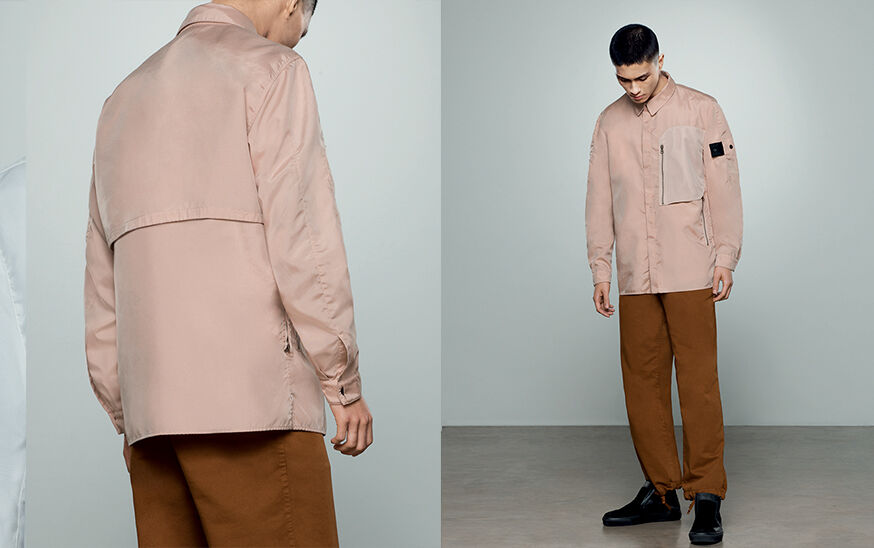 Two shots of the same model, showing the back close up and the front full body, wearing tan pants and a beige overshirt with an off white chest pocket with zipper fastening and the Stone Island Shadow Project badge on the upper left sleeve.