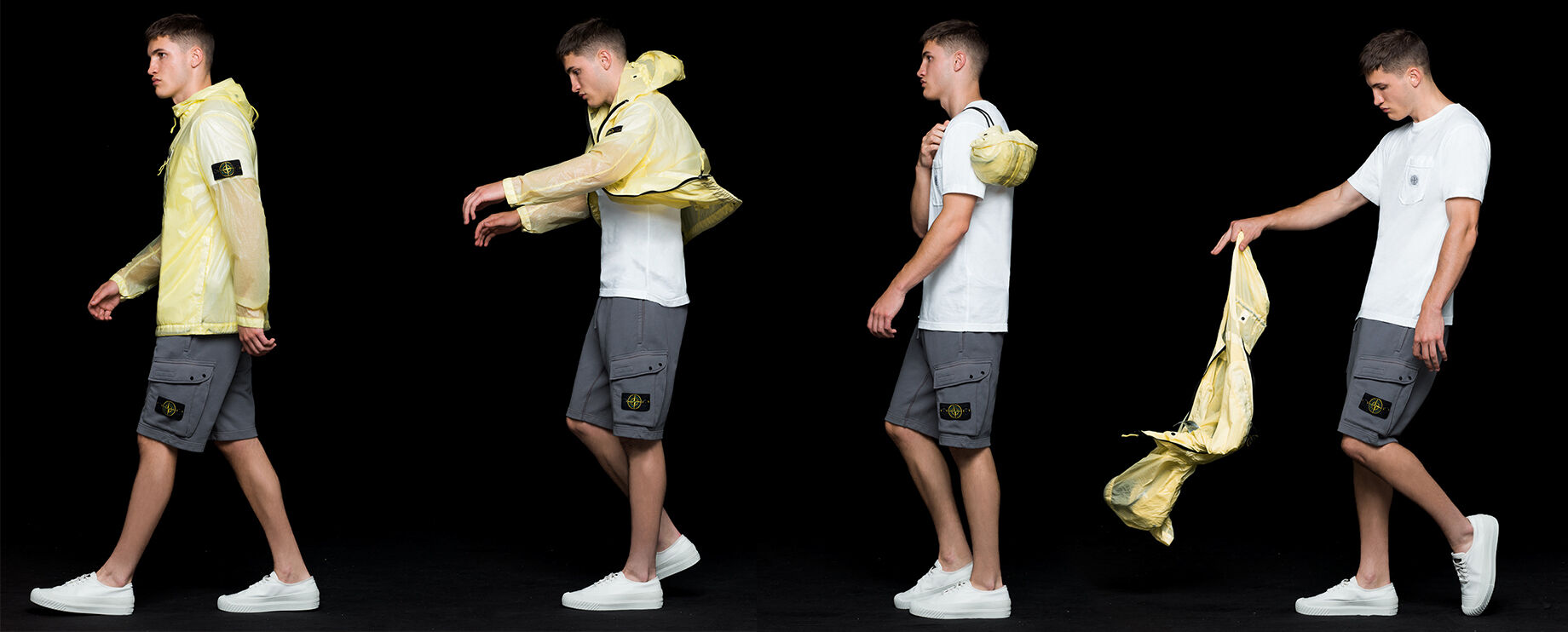Four shots of the same model wearing gray cargo shorts, a white crewneck T shirt and a yellow see through hooded jacket with shiny effect, showing that the jacket is pocketable and can be stored in a carrying pouch.