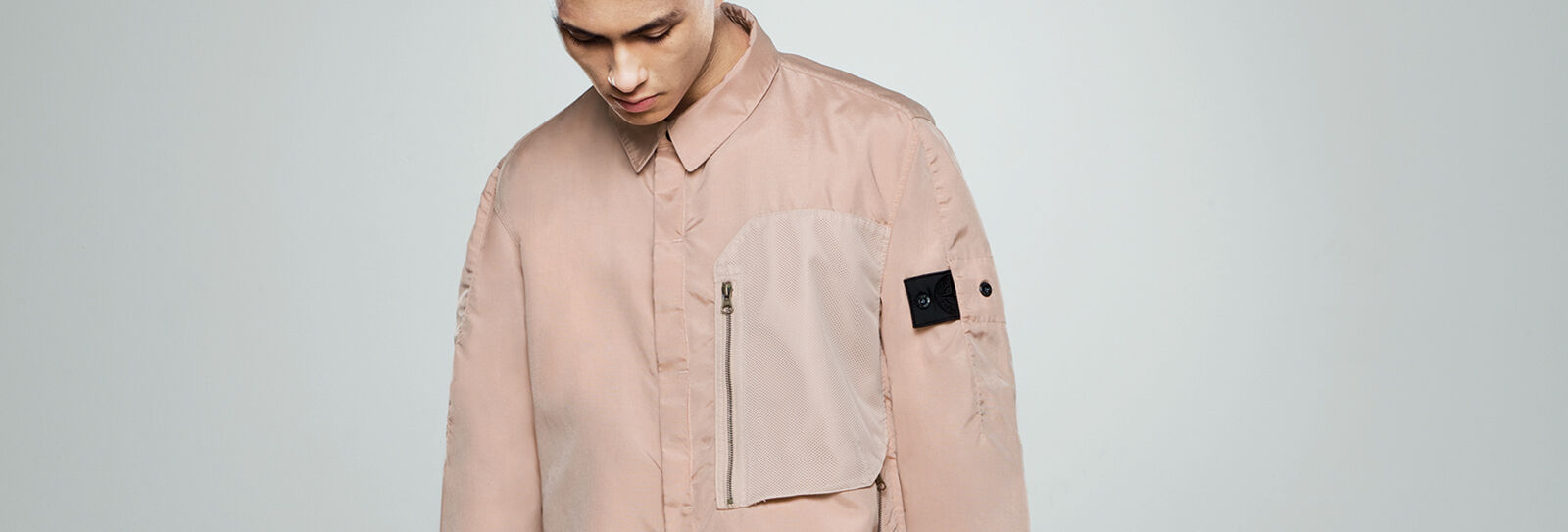 Close up shot of model wearing a beige overshirt with an off white chest pocket with zipper fastening and the Stone Island Shadow Project badge on the upper left sleeve.
