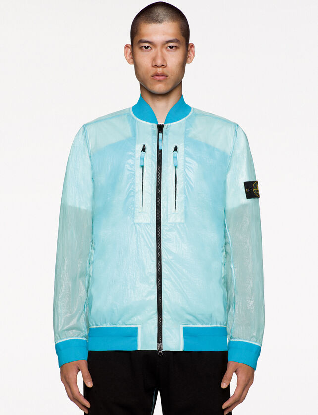 Model wearing black pants and a light blue see through bomber jacket with shiny effect, two way black zipper fastening, two vertical chest pockets with zipper and the Stone Island badge on the upper left arm.