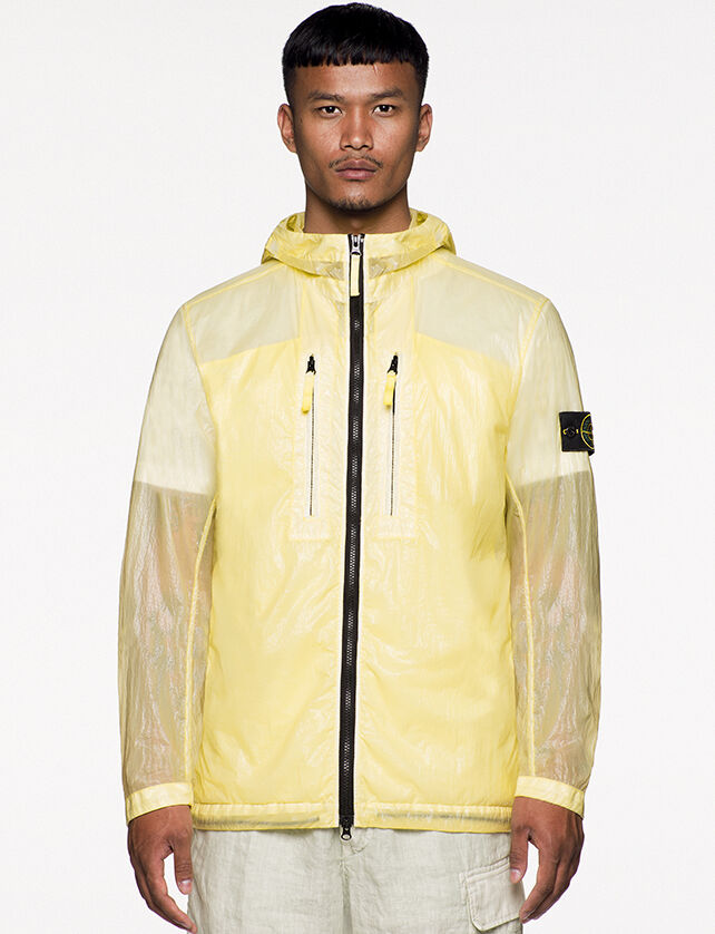 Model wearing off white pants and a yellow see through hooded jacket with shiny effect, two way black zipper fastening, two vertical chest pockets with zipper and the Stone Island badge on the upper left arm.