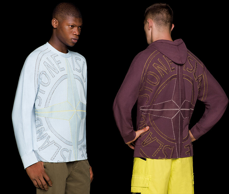 Two models, one wearing military green pants and a light blue crewneck knit with long sleeves and a large Stone Island compass rose logo embroidery on the front, the other seen from the back, wearing yellow cargo pants and a dark burgundy hooded knit with