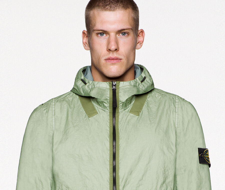 Close up of model wearing a light green jacket with darker green edging details, hood with drawstring, black zipper fastening and the Stone Island badge on the upper left arm.