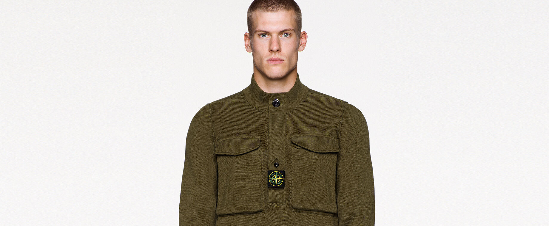 Model wearing military green pants and a matching knit sweater with standing collar, button fastening placket with a buttoned central strap on the chest featuring the Stone Island badge, two chest patch pockets with flap and ribbed cuffs.
