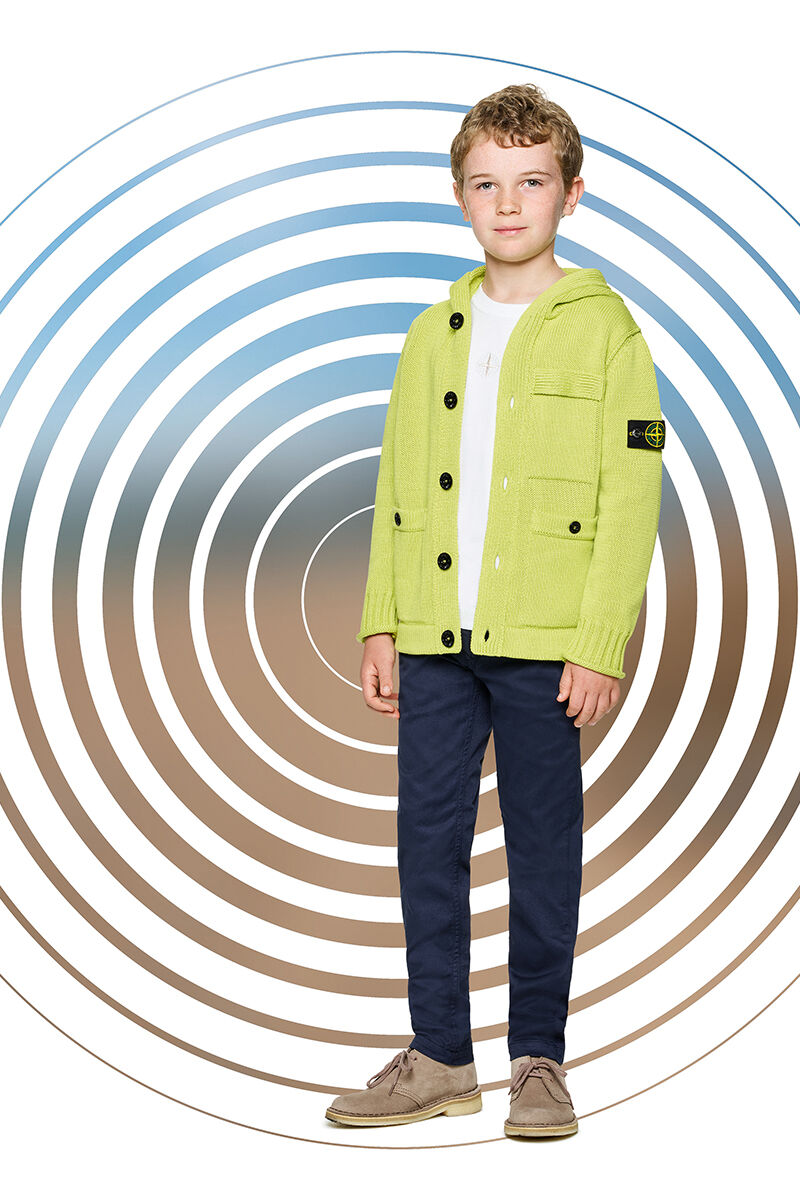 Junior model against a multicolor spiral backdrop, wearing dark blue pants, a white t shirt and a lime yellow sweater with hood, black buttons fastening, one chest pocket and two patch pockets with button.