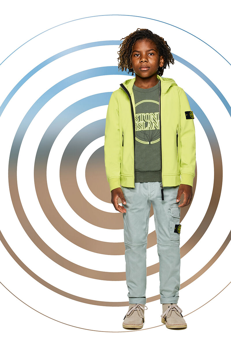 Junior model against a multicolor spiral backdrop, wearing khaki cargo pants, a military green crewneck sweatshirt with Stone Island print and a lime yellow jacket with hood and zipper fastening.