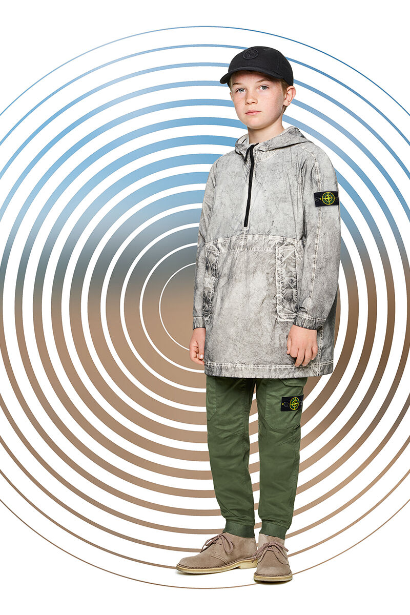 Junior model against a multicolor spiral backdrop, wearing green cargo pants, a black cap and a light gray dust effect parka with hood, half zip fastening and slanting hand pockets.