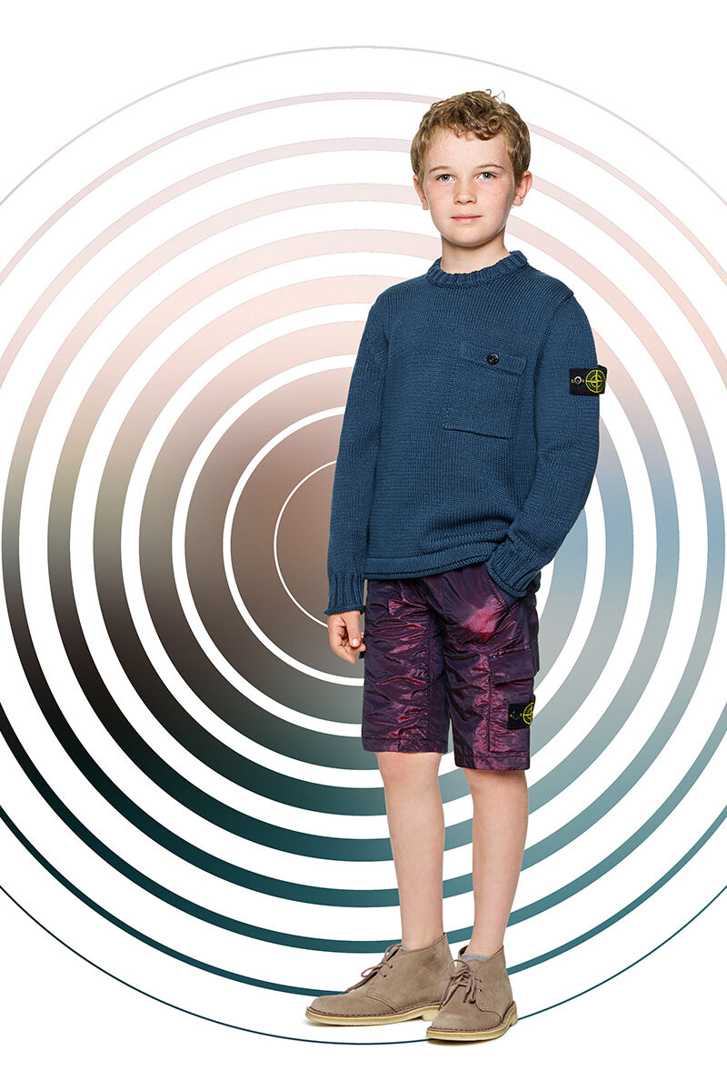 Junior model against a multicolor spiral backdrop, wearing metallic effect purple cargo shorts and a teal crewneck sweater with a chest pocket and the Stone Island badge on the upper left sleeve.