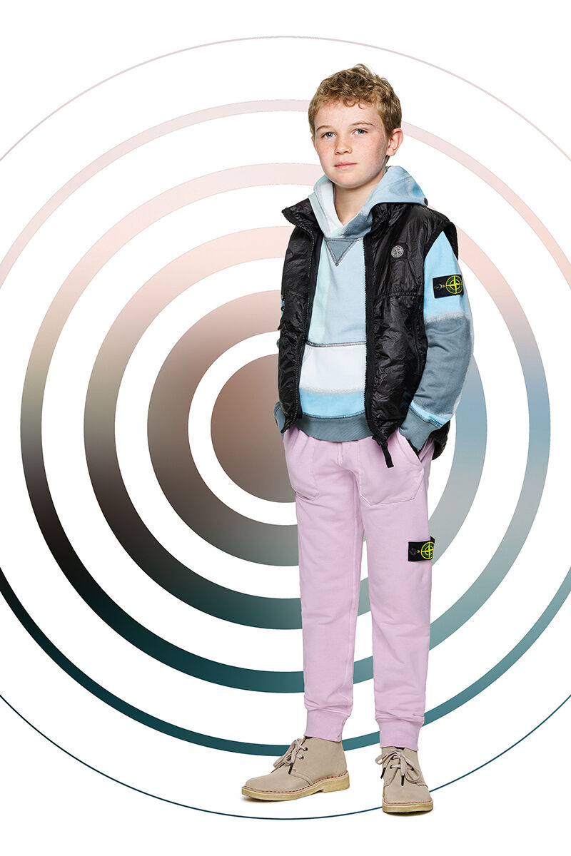 Junior model against a multicolor spiral backdrop, wearing light lilac joggers, a hooded sweatshirt in different hues of blue and a black vest with stand up collar and zipper fastening.