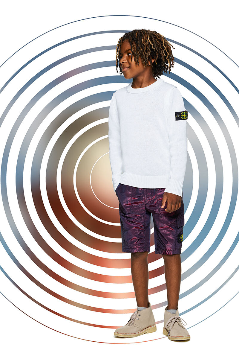 Junior model against a multicolor spiral backdrop, wearing metallic effect purple cargo shorts and a white crewneck sweater with ribbed cuffs and bottom band and the Stone Island badge on the upper left sleeve.