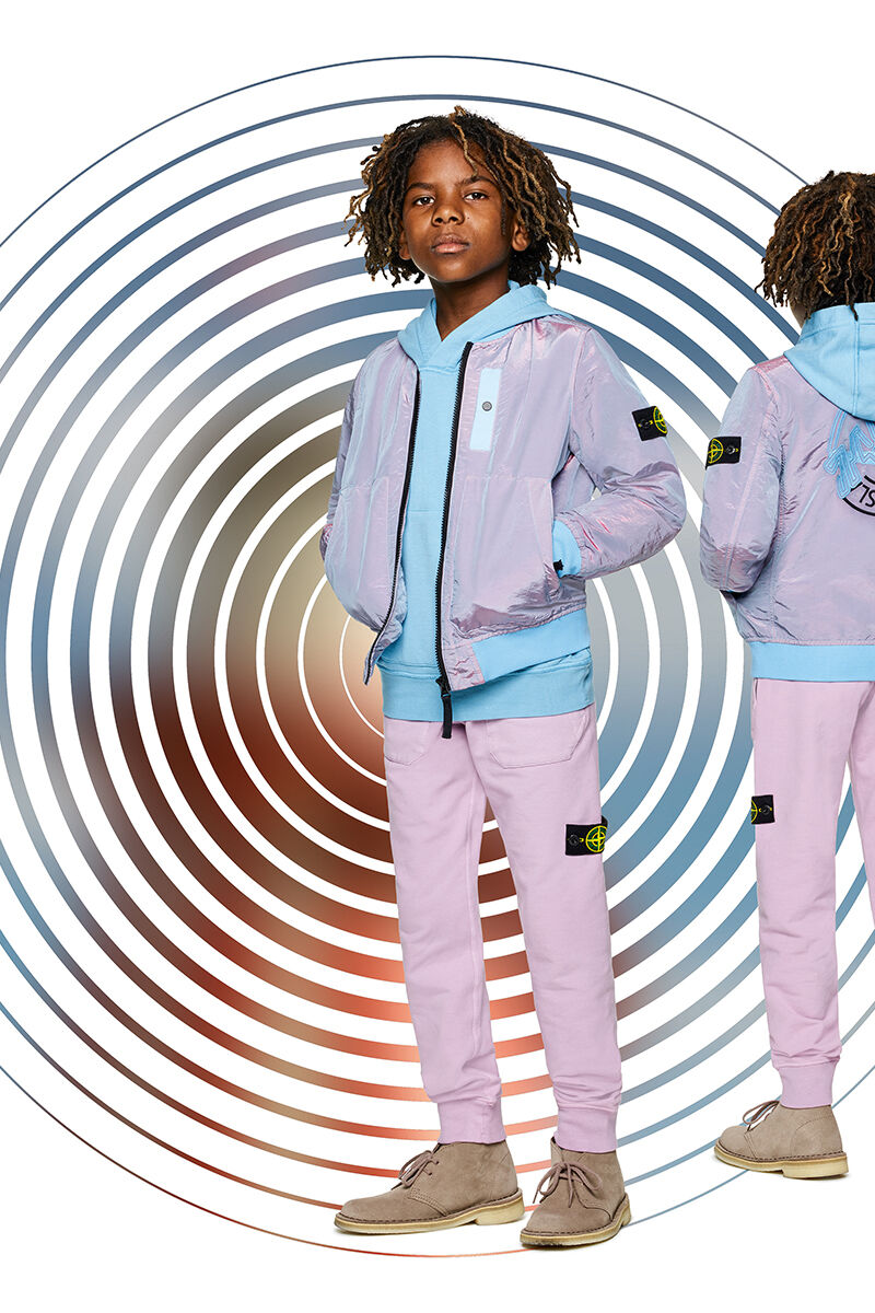 Two shots of the same junior model showing the front and back against a multicolor spiral backdrop, wearing lilac joggers, a light blue hooded sweatshirt and a lilac and light blue bomber jacket with zipper fastening and a Stone Island logo on the back.