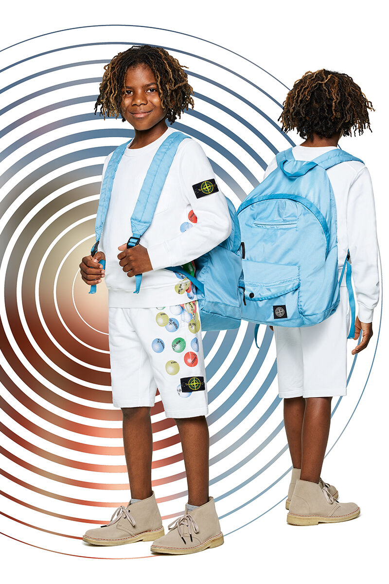 Two shots of the same junior model showing the front and back against a multicolor spiral backdrop, wearing white shorts with a colorful ball print, a matching crewneck sweatshirt and a light blue backpack with adjustable shoulder straps.