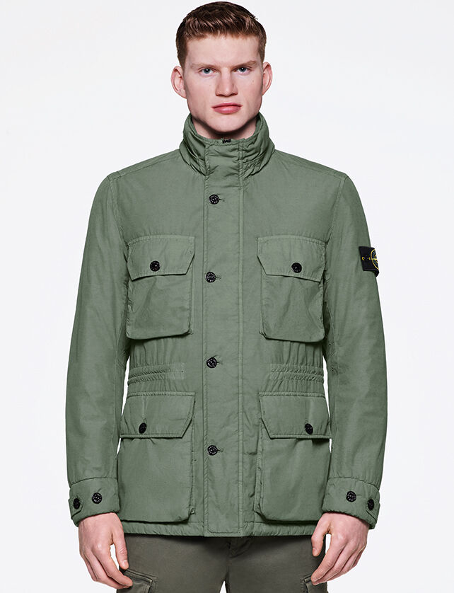 Model wearing military green pants and a lighter green field jacket with standing collar, button fastening, four pockets with flap and button and drawstring at waist.