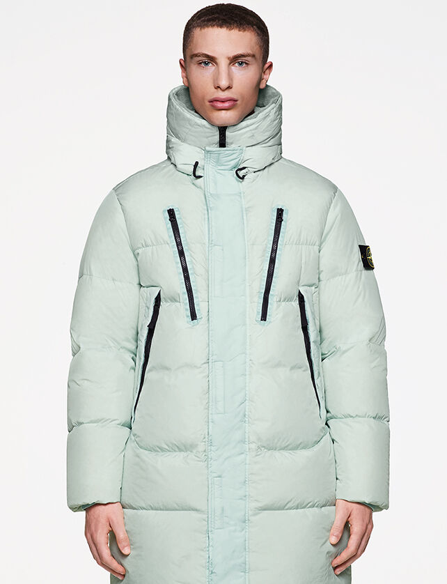 Model wearing a long down jacket in aqua color, with a standing collar, fastening hidden by a flap and four diagonal chest pockets with black zipper.