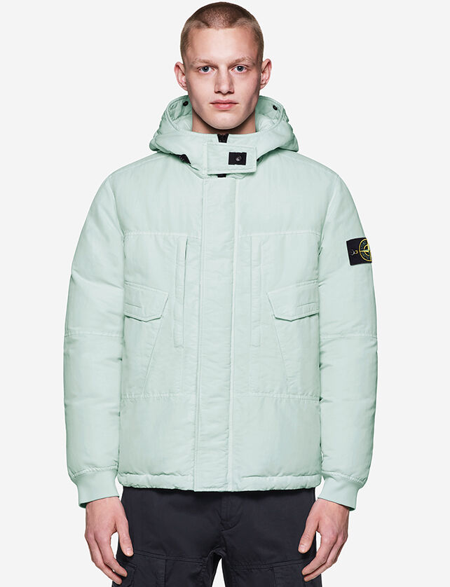 Model wearing dark colored cargo pants and an aqua jacket with hood, fastening hidden by a flap, chest pockets with flap and the Stone Island badge on the upper left sleeve.