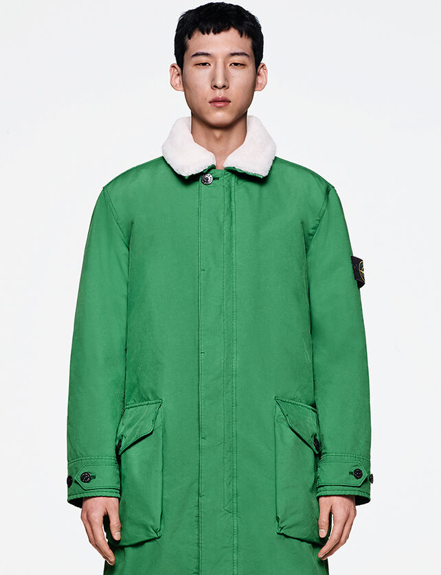 Model wearing a bright green long coat with adjustable straps at cuffs, a white lined collar, fastening hidden by a flap and two big pockets with flap and button.
