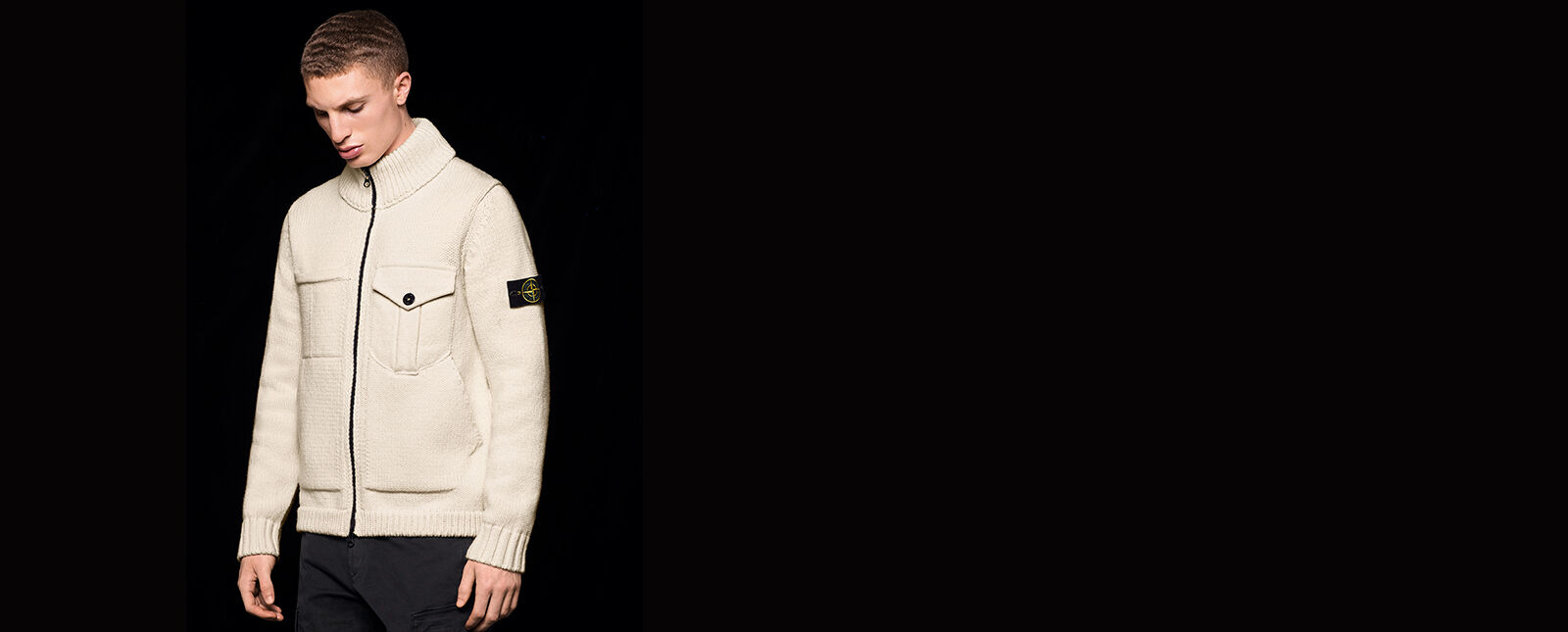 Model wearing black pants and an off white knit sweater with two way zipper fastening, one chest pocket with flap, ribbed cuffs, bottom hem and collar and the Stone Island badge on the upper left sleeve.
