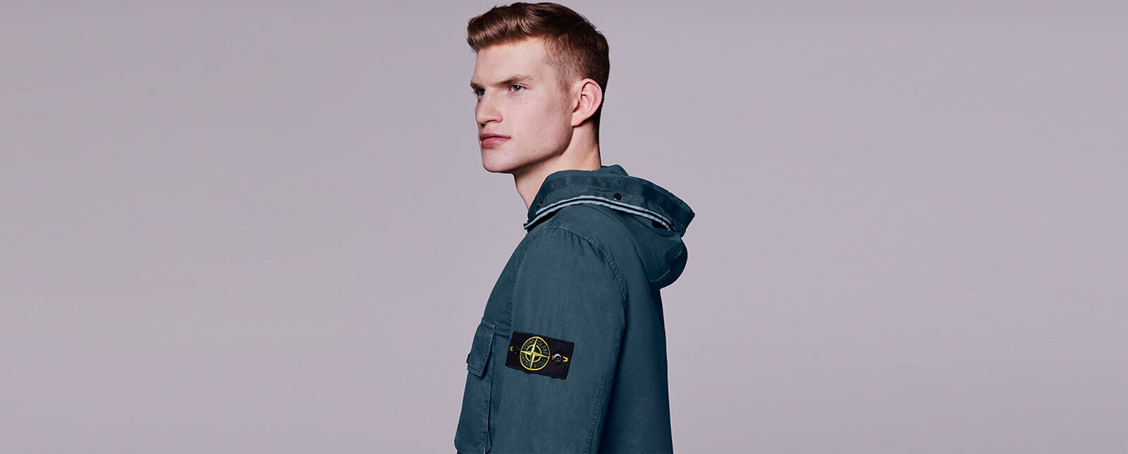 Side view of model wearing a dark blue overshirt with a chest pocket with flap, a hood edged with two parallel light blue strips and the Stone Island badge on the upper left sleeve.