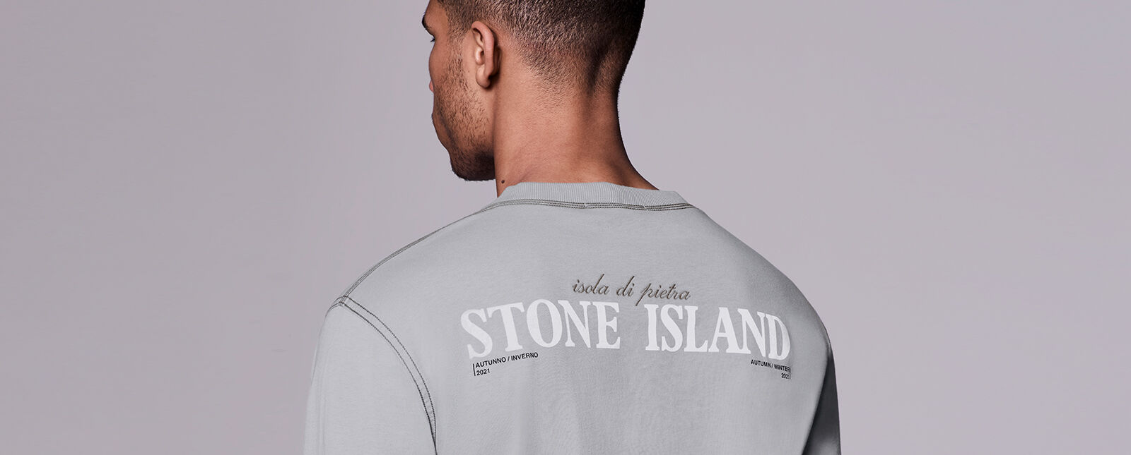 Close up shot of model showing the back of a light gray shirt with contrast dark stitching and lettering that reads isola di pietra STONE ISLAND AUTUNNO / INVERNO 2021 AUTUMN / WINTER 2021.