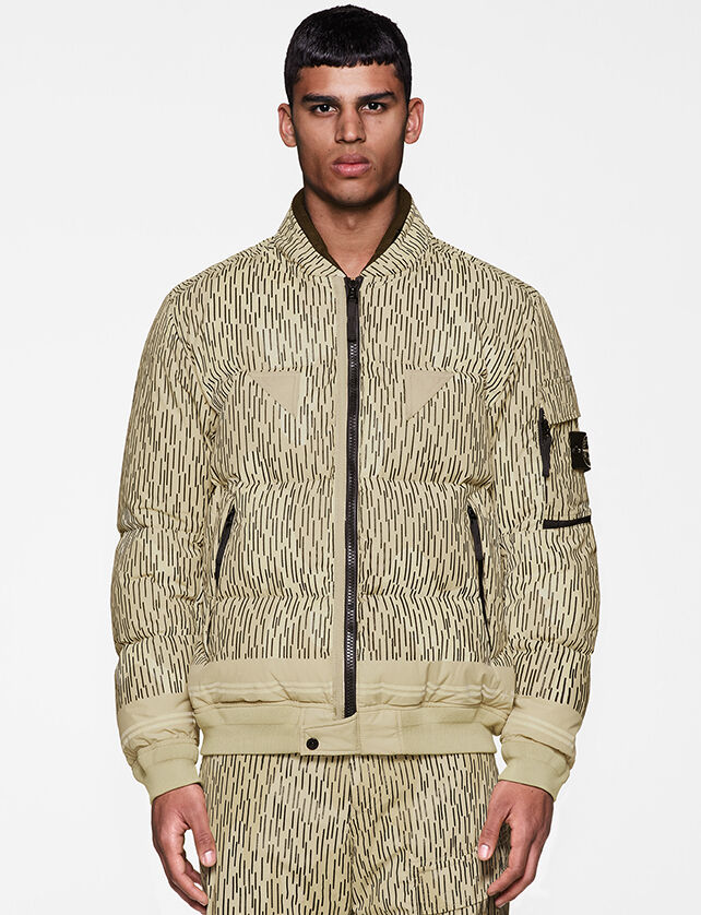Model wearing beige and black print pants and a matching down jacket with black zipper fastening, elasticated cuffs and bottom hem and a pocket with flap and the Stone Island badge on the upper left sleeve.