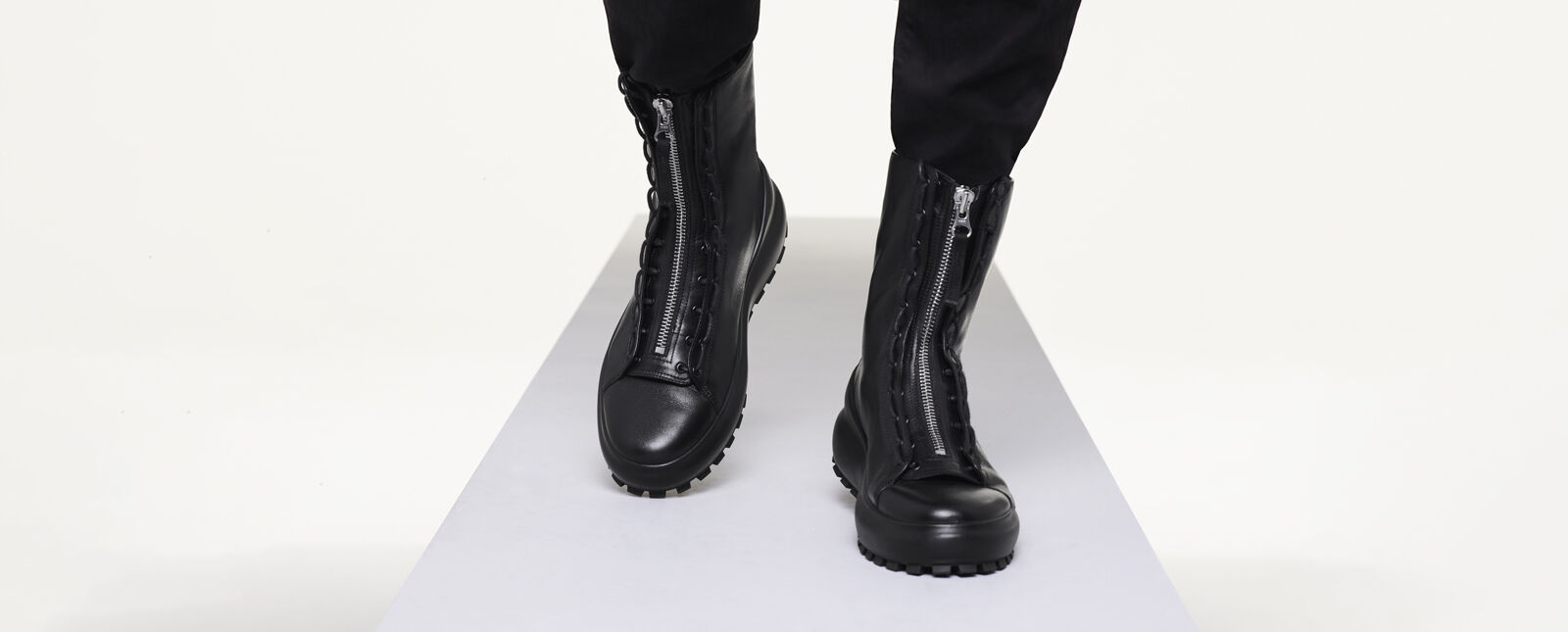 Close up shot of model wearing black pants inside military style black boots with chunky sole and metal zipper fastening.
