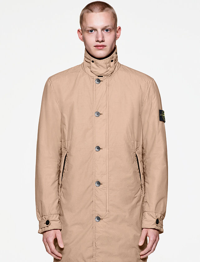 Model wearing a long beige trench coat with standing collar, button fastening, two side pockets and strap at cuffs, held by an adjustable snap.