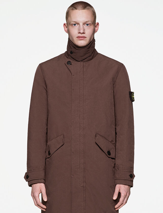 Model wearing a long brown coat with standing collar, fastening hidden by a flap, two hand pockets and the Stone Island badge on the upper left sleeve.