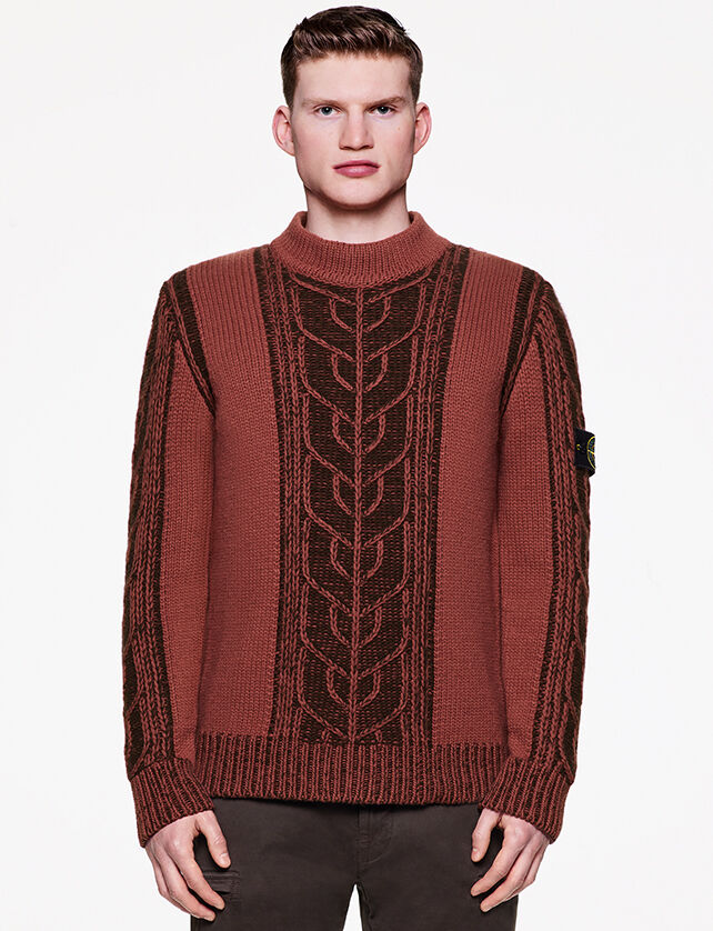 Model wearing dark colored pants and a dark red knit sweater with a braided motif, the Stone Island badge on the upper left sleeve and ribbed neckline, bottom hem and cuffs.