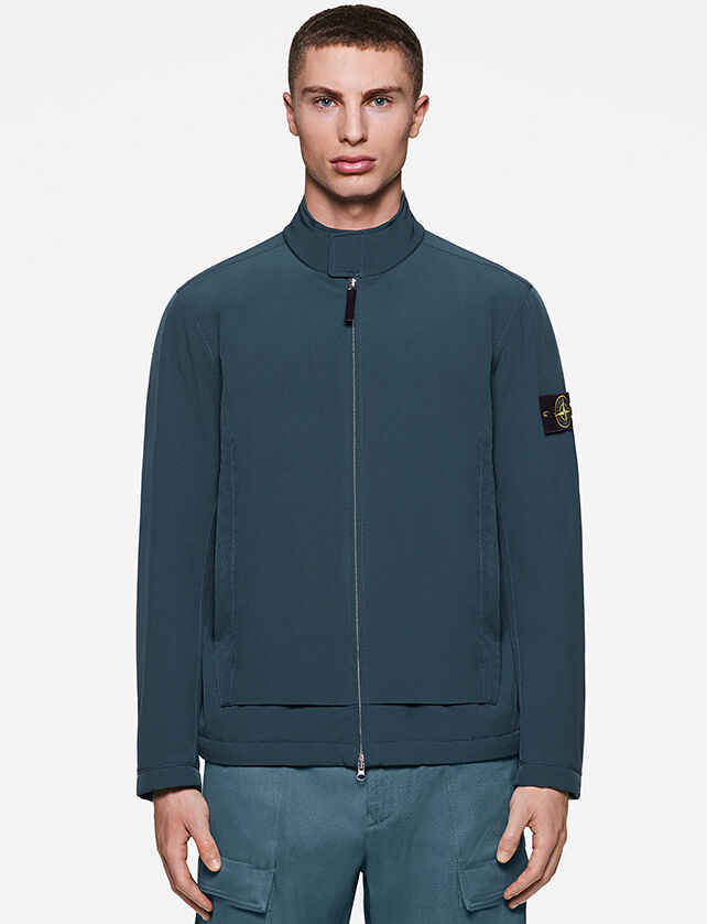 Model wearing light teal colored cargo pants and a darker teal light jacket with two way zipper fastening, standing collar with flap and the Stone Island badge on the upper left sleeve.