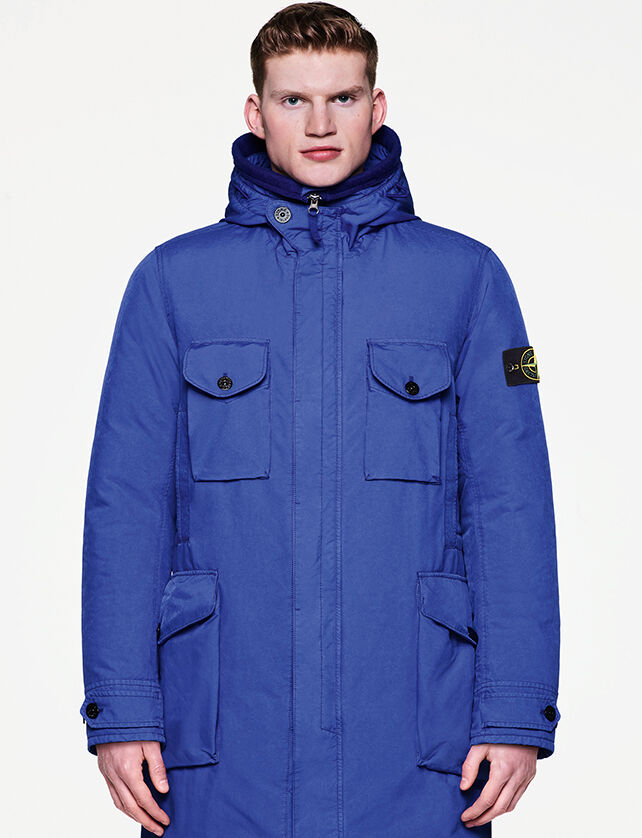Model wearing a hooded long parka in a bright blue color, with fastening hidden by a flap, four pockets with flap and button and the Stone Island badge on the upper left sleeve.