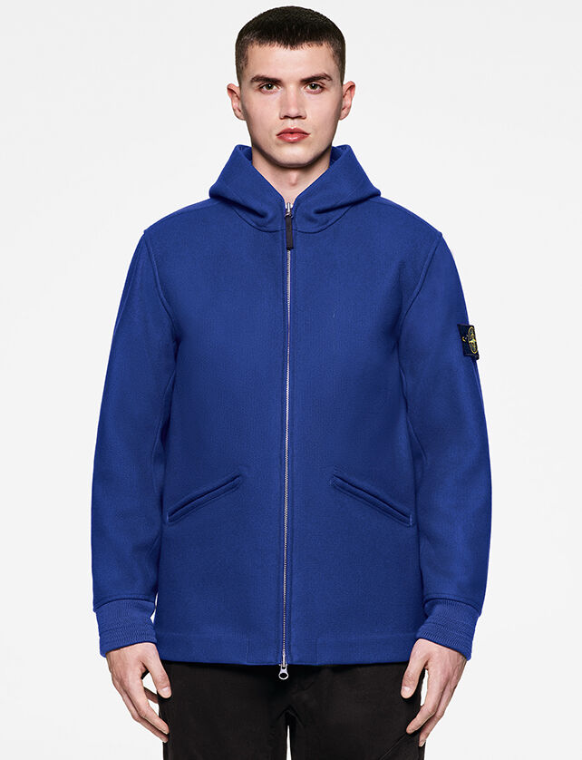 Model wearing black pants and a bright blue hooded jacket with two way zipper fastening, two diagonal hand pockets and the Stone Island badge on the upper left sleeve.