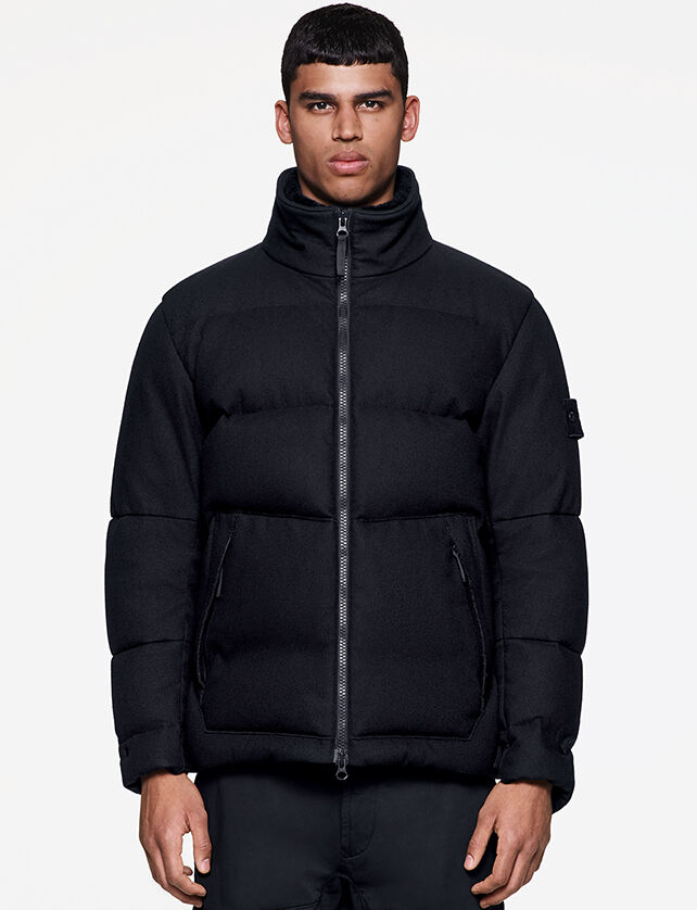 Model wearing dark colored pants and a black down jacket with standing collar, a two way zipper fastening, two side pockets with zipper and the Stone Island ghost badge on the upper left sleeve.