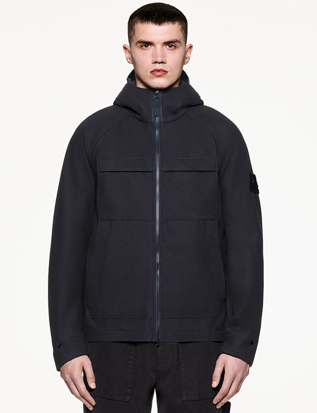 Model wearing dark colored pants and a matching jacket with hood, two way zipper fastening, two chest pockets with flap and the Stone Island ghost badge on the upper left sleeve.