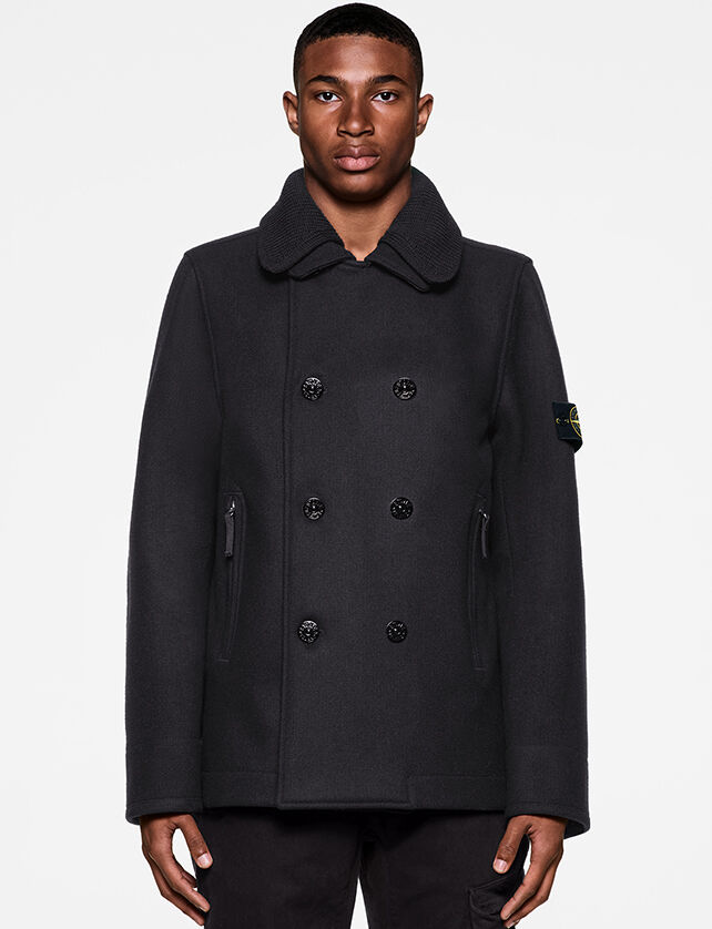 Model wearing dark colored pants and a matching pea coat with double collar, double breasted buttoning, two side hand pockets with zipper and the Stone Island badge on the upper left sleeve.