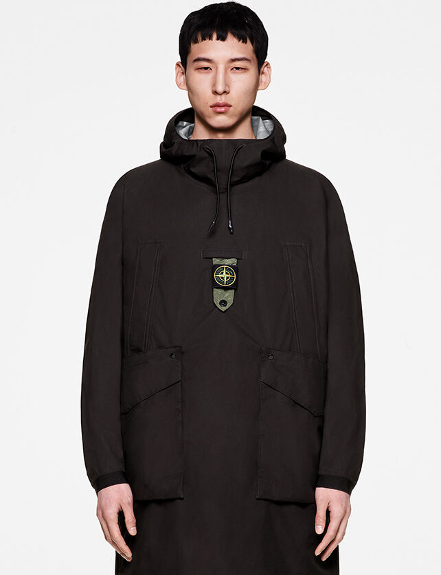 Model wearing a long black anorak with hood with drawstring, two side chest pockets, two front hand pockets with flap and central buttoned strap bearing the Stone Island badge.