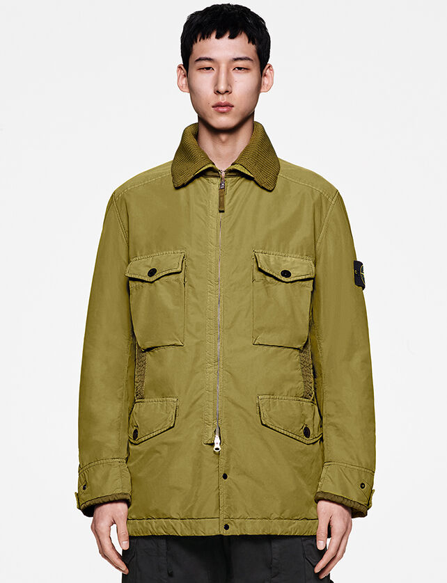 Model wearing black pants and an olive green field jacket with ribbed collar, two bellows pockets on the chest, two way zipper fastening and two bellows hand pockets with flap and button.