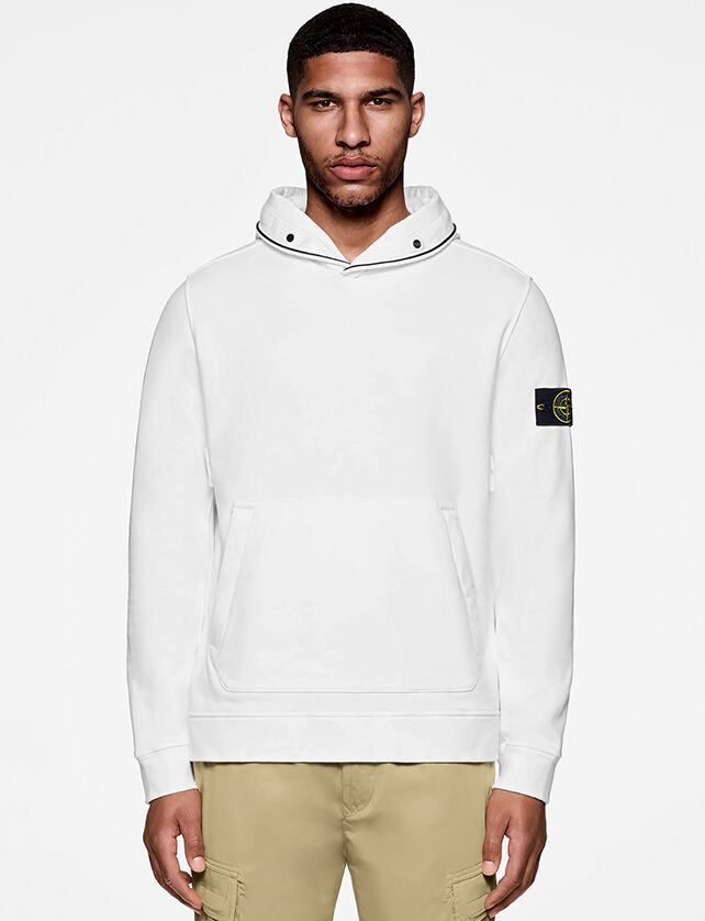 Model wearing hooded white sweatshirt and sand color pants.