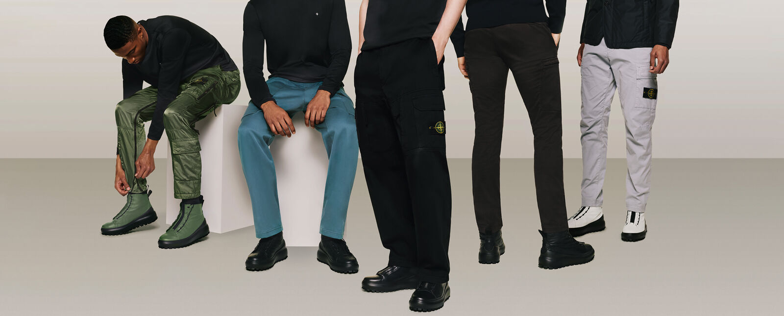 Five models wearing black tops and cargo pants in different styles and colors, shiny green, teal blue, black and light gray.