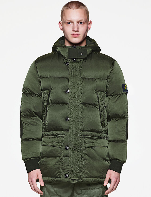 Model wearing military green pants and a matching down jacket with shiny effect, a hood with frontal flap, button fastening, two side pockets at chest and elasticated cuffs.