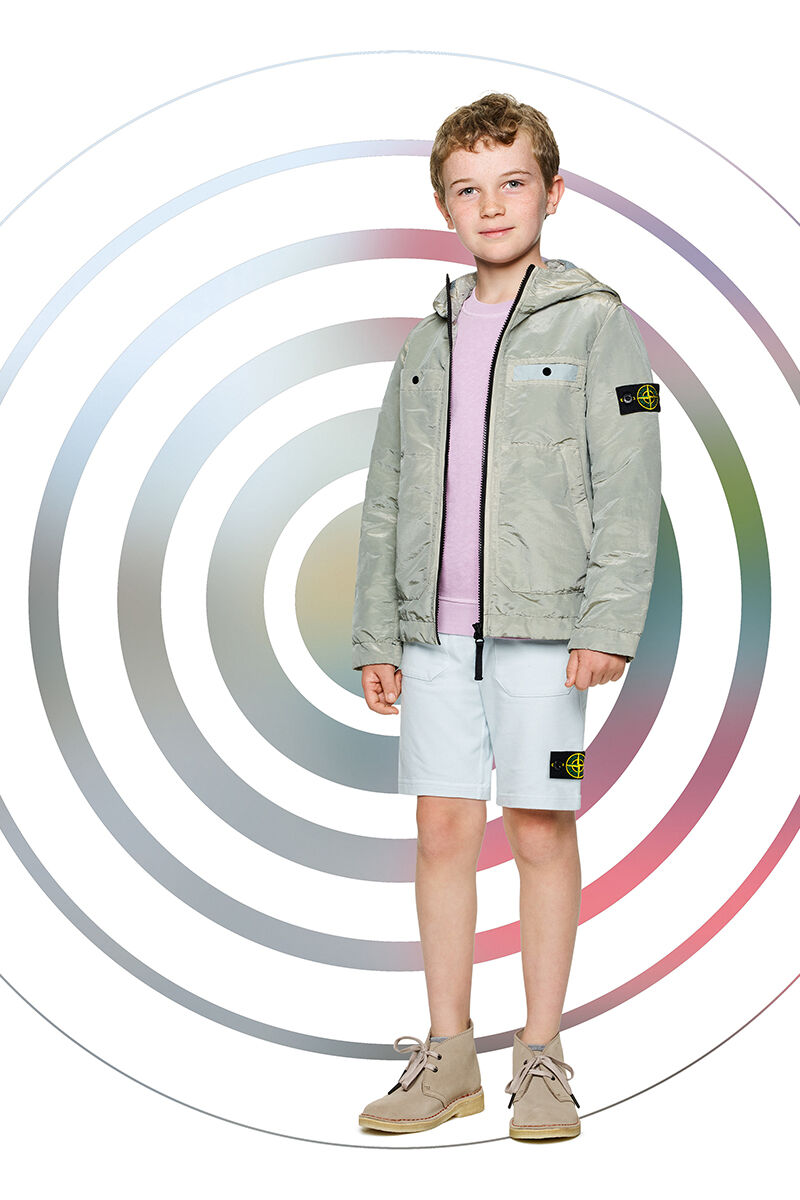 Junior model against a multicolor spiral backdrop, wearing off white shorts, a light lilac crewneck sweatshirt and a khaki colored hooded jacket with zipper fastening and two chest pockets.