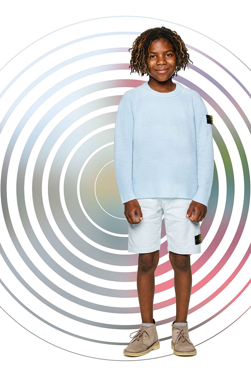 Junior model against a multicolor spiral backdrop, wearing off white shorts, a light blue crewneck sweater with ribbed cuffs and bottom band and the Stone Island badge on the upper left sleeve.