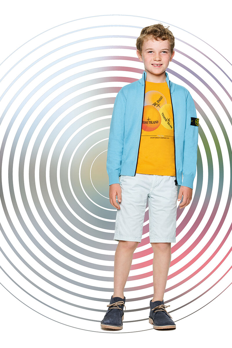 Junior model against a multicolor spiral backdrop, wearing off white shorts, a yellow T shirt with a Stone Island print and a light blue sweater with standing collar and zipper fastening.