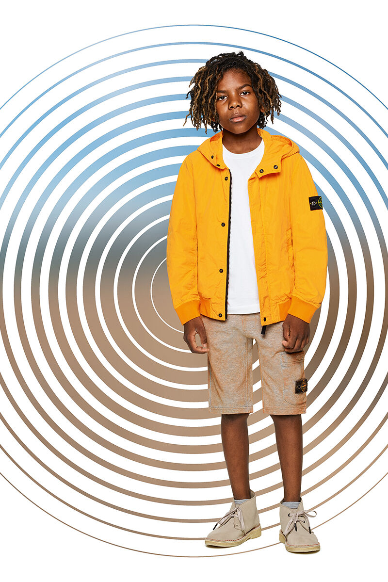 Junior model against a multicolor spiral backdrop, wearing orange cargo shorts, a white t shirt and a bright yellow jacket with hood, zipper and snap buttons fastening.