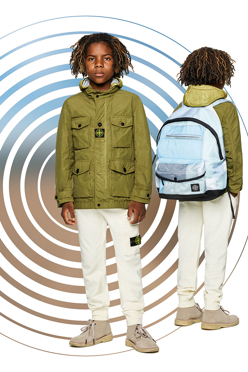 Two shots of the same junior model showing the front and back against a multicolor spiral backdrop, wearing off white cargo pants, a military green field jacket with hood and a light blue backpack with black details.