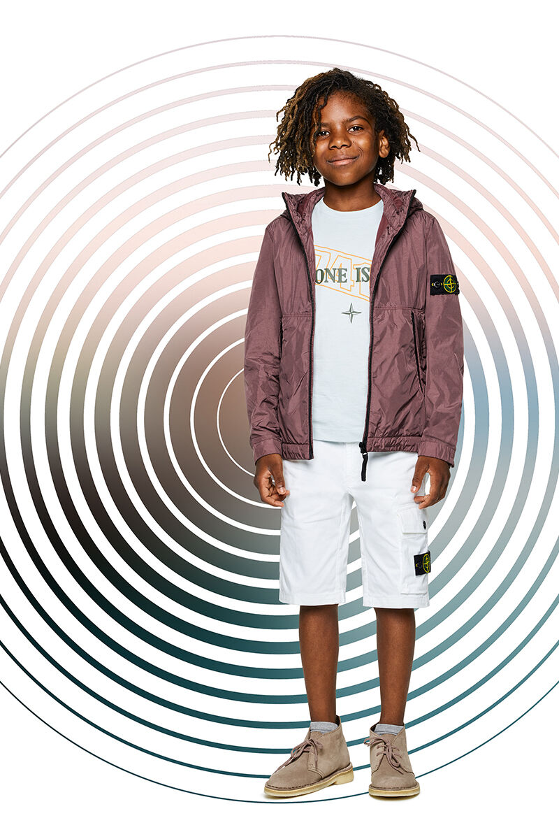 Junior model against a multicolor spiral backdrop, wearing white cargo shorts, an off white t shirt with the Stone Island logo and a hooded burgundy jacket with zipper fastening.