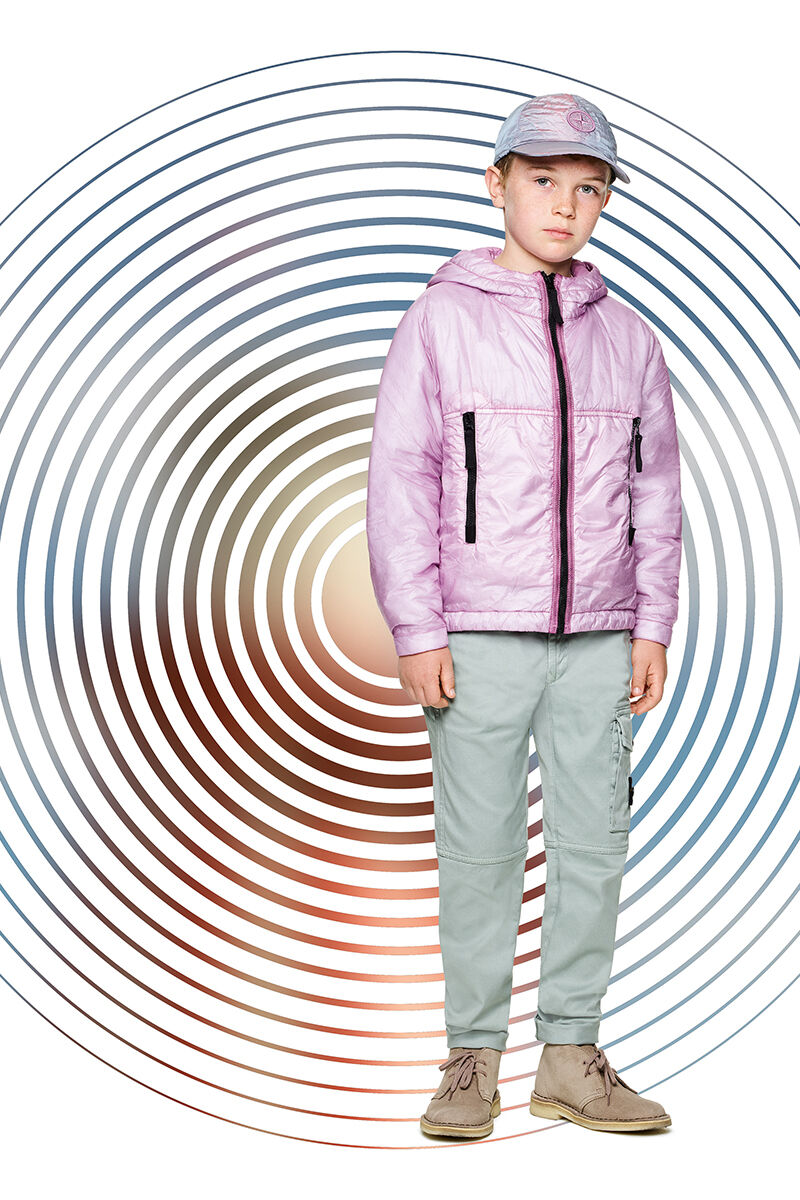 Junior model against a multicolor spiral backdrop, wearing green cargo pants, a pink hooded jacket with black zipper fastening and a pink and light blue cap with the Stone Island compass rose logo.