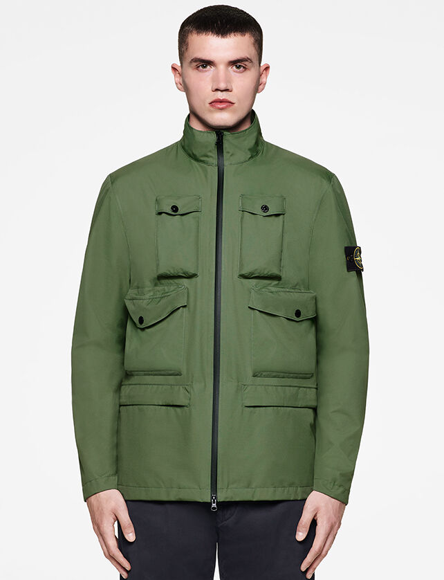 Model wearing dark colored pants and a green jacket with standing collar, black two way zipper fastening, four pockets with flap and button on the chest and the Stone Island badge on the upper left sleeve.